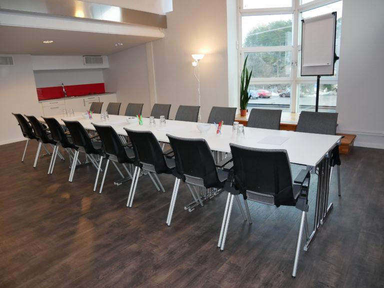 Långt konferensbord med svarta stolar uppställt i ett konferensrum