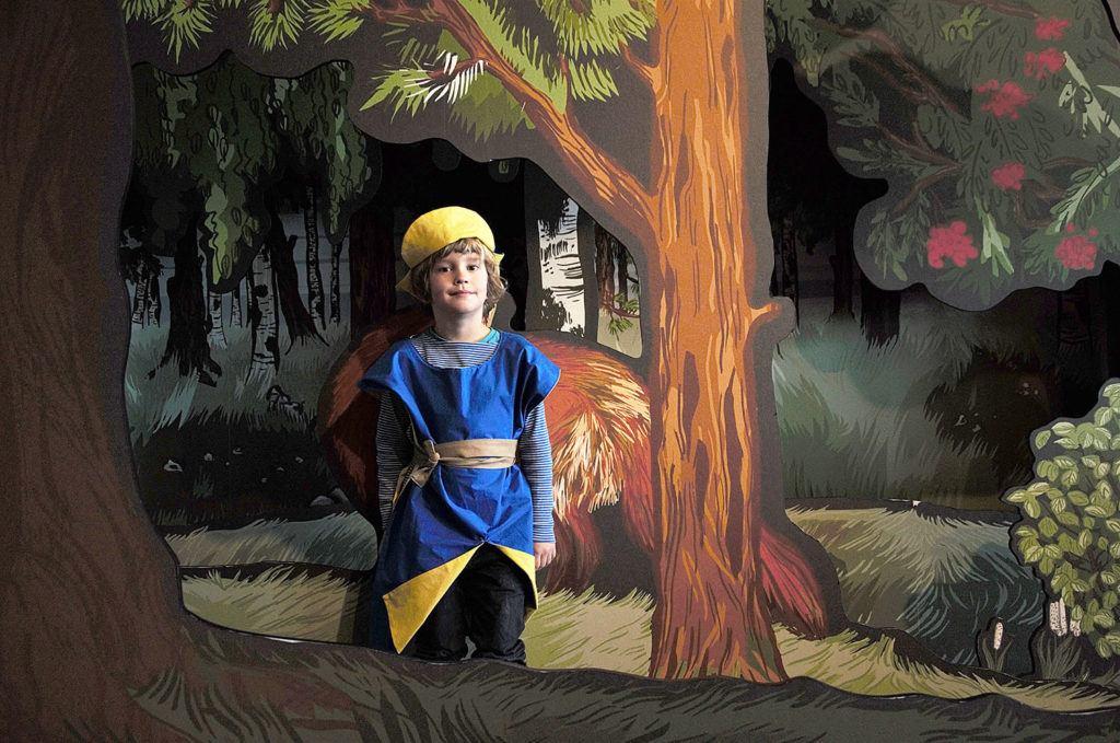 Ett barn klädd som Karolin i gult och blått.