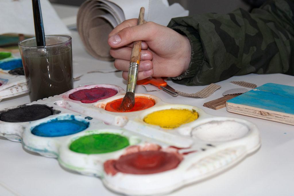 En palett med olika vattenfärger ligger på ett bord. En barnhand tar röd färg med pensel.
