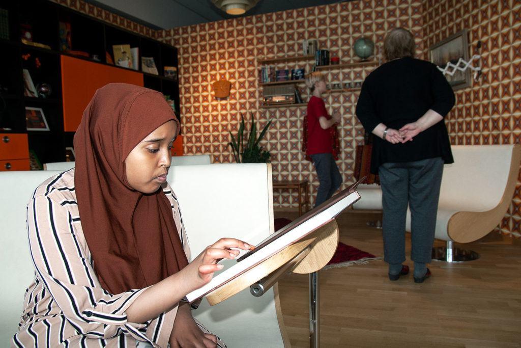 Rum med 70-talsinredning. I förgrunden sitter en flicka som använder en pekskärm.