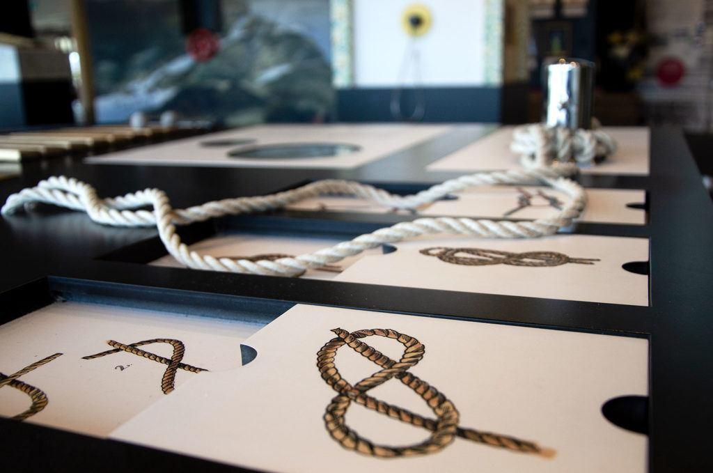 Bord med illustrationer av knopar samt rep för att knyta knopar