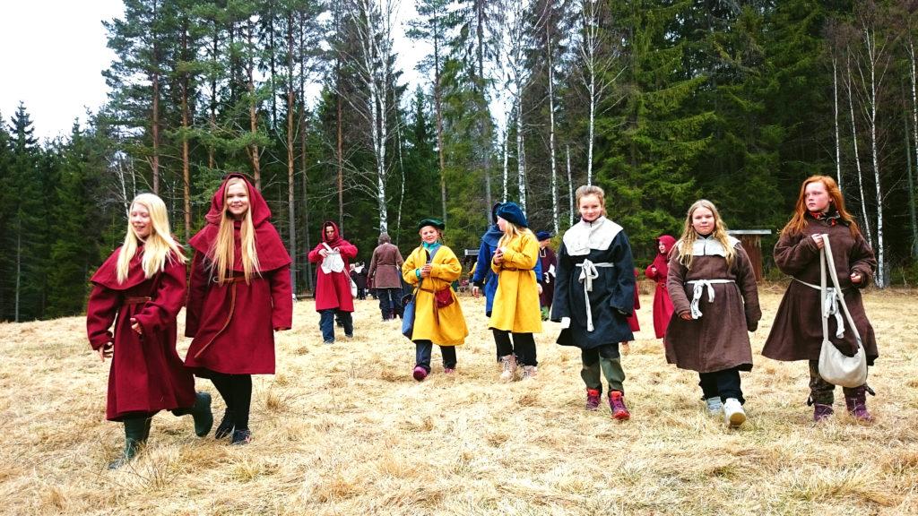 Barn i forntida kläder går på en öppen gräsyta med skog i bakgrunden