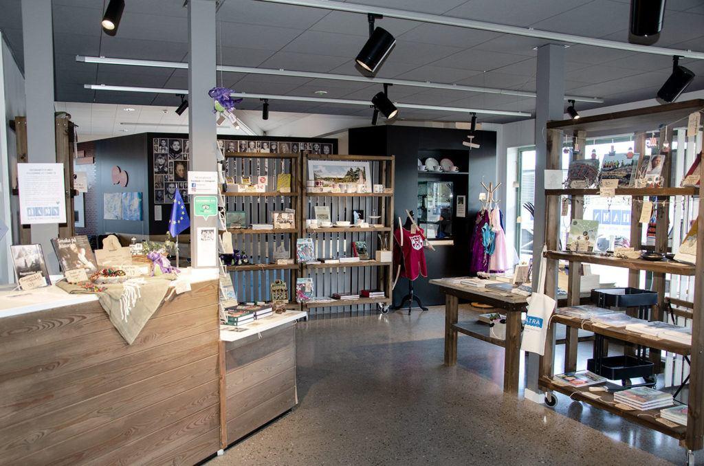 Foto inifrån museibutiken. Utmed väggarna står hyllor med produkter.