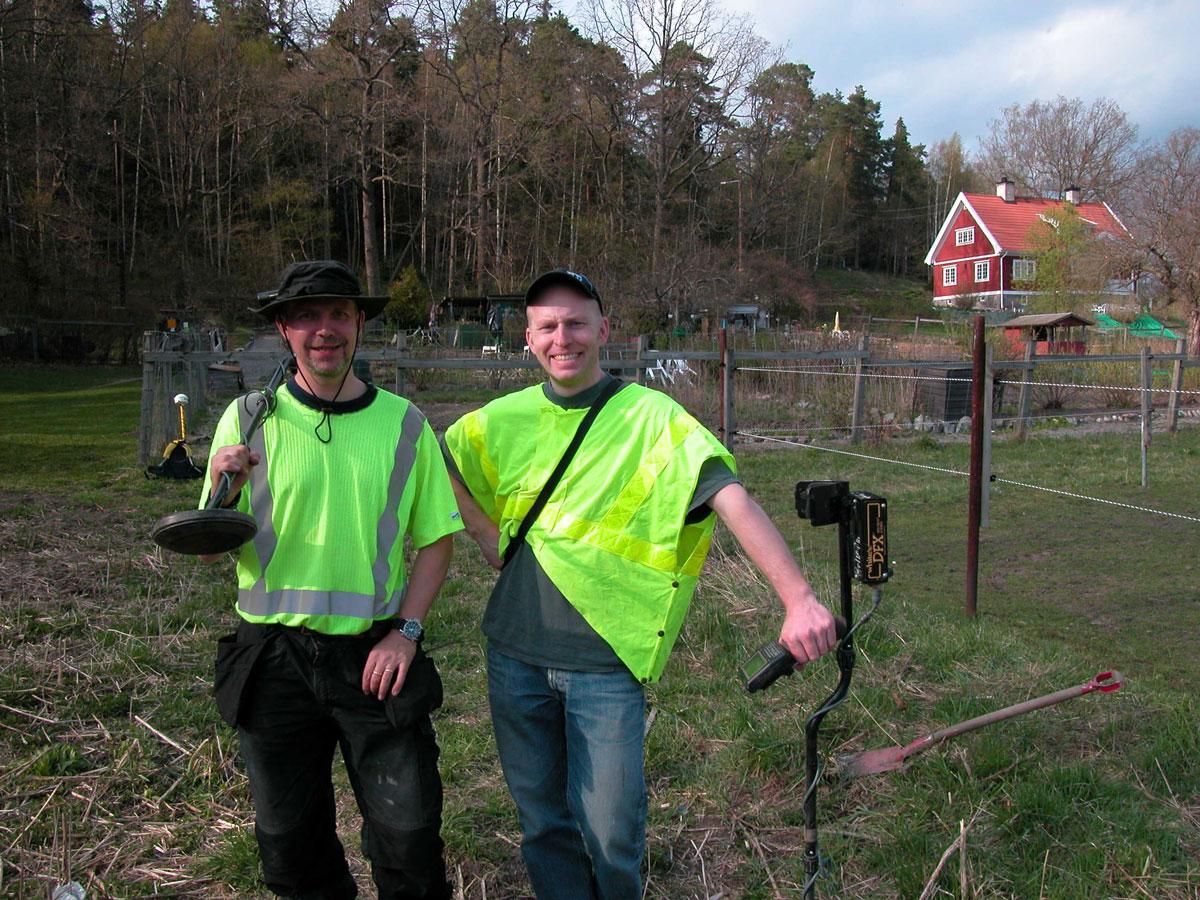 Två män i reflexvästar står ute på ett fält med skog i bakgrunden