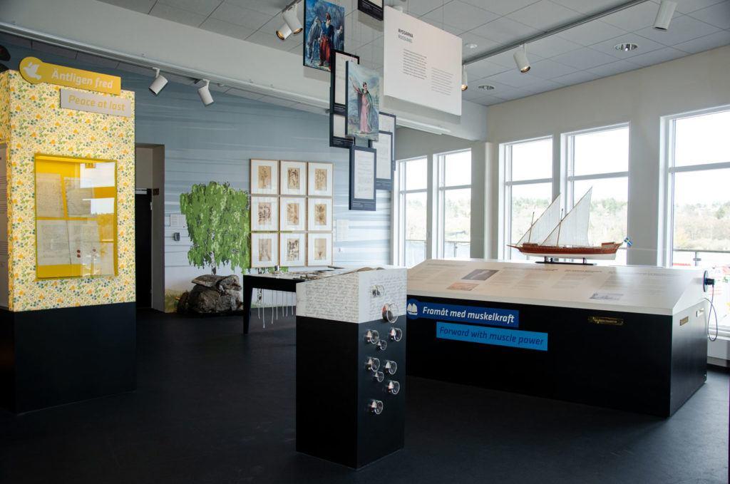 Rum med stora fönster ut mot vattnet. I rummet ser man delar av Museet HAMNs utställing.