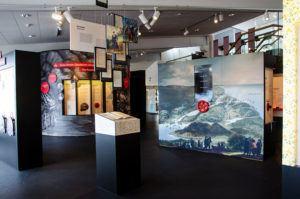 Bild från museet. Till höger en vägg med en större landskapsmålning. Mitt på målningen sitter en röd ratt.