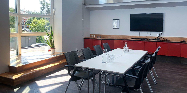 Konferensrum med stora fönster och bord och stolar i mitten